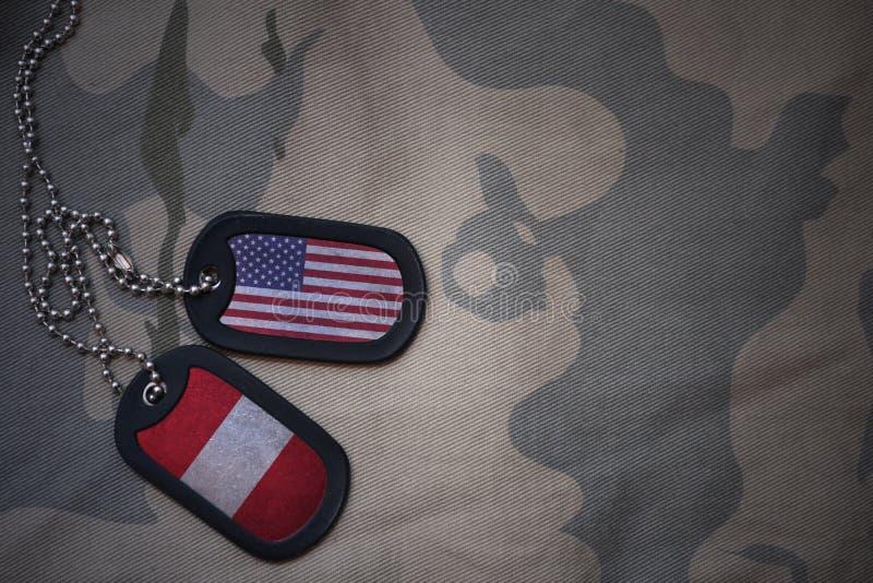 wojska puste miejsce, psia etykietka z flaga zlani stany America i Peru na khakim tekstury tle, obraz royalty free