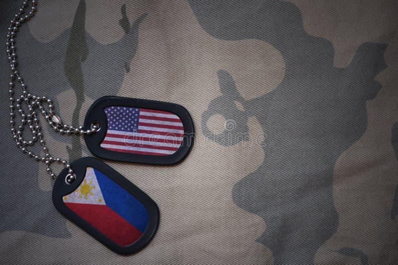 wojska puste miejsce, psia etykietka z flaga zlani stany America i Philippines na khakim tekstury tle, obraz royalty free
