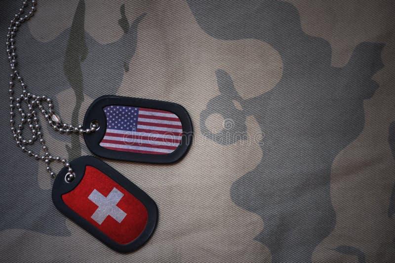 wojska puste miejsce, psia etykietka z flaga zlani stany America i Switzerland na khakim tekstury tle, obrazy royalty free