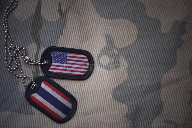 wojska puste miejsce, psia etykietka z flaga zlani stany America i Thailand na khakim tekstury tle, zdjęcie stock
