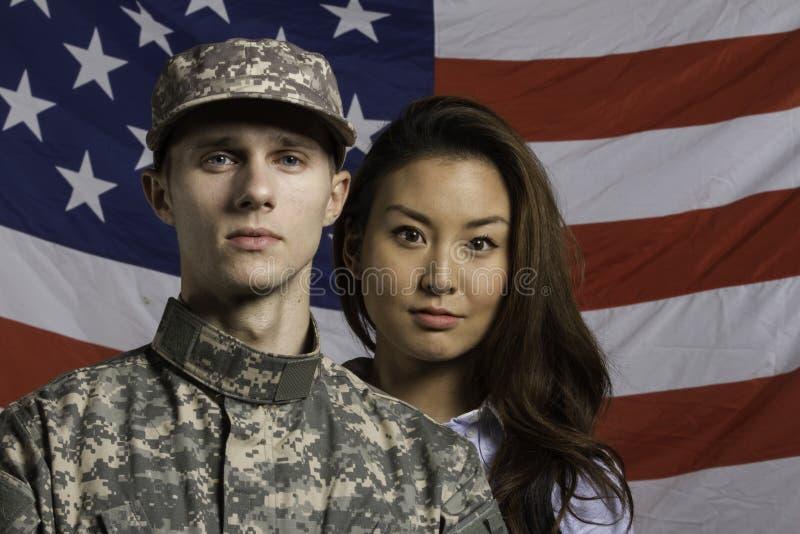Wojskowy i jego żona przed USA flaga, horyzontalną fotografia royalty free