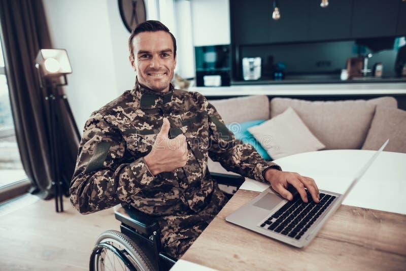 Wojskowy w wózku inwalidzkim Używa laptop aprobaty obrazy royalty free