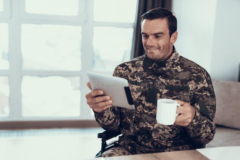 Wojskowy w wózku inwalidzkim Używa pastylkę i Pije herbaty fotografia stock
