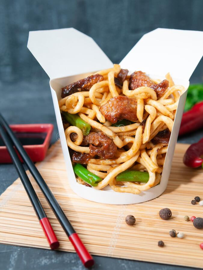 Free Wok Box With Noodles Oyster Sauce And Coconut Milk, Beef, Wood Mushroom, Green Beans..The Wok Box Is Cut. Standing On A Mat Next Royalty Free Stock Image - 170812226