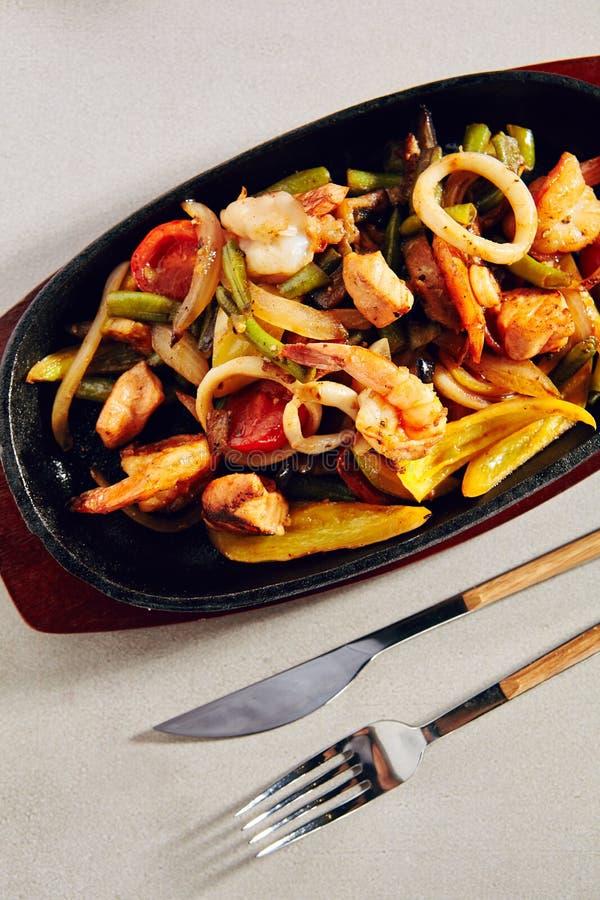 Wok con le verdure arrostite, gamberetti della tigre o gamberetti ed anelli del calamaro fotografia stock libera da diritti