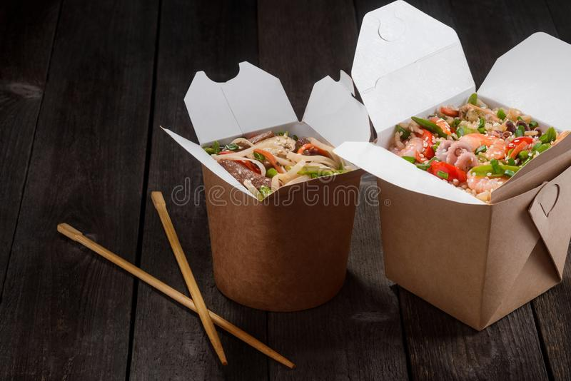 Wok noodles and rice. Yummy and nourishing exotic dishes with seafood and vegetables, chopsticks to eat that food. Delivered from Chinese restaurant royalty free stock photos