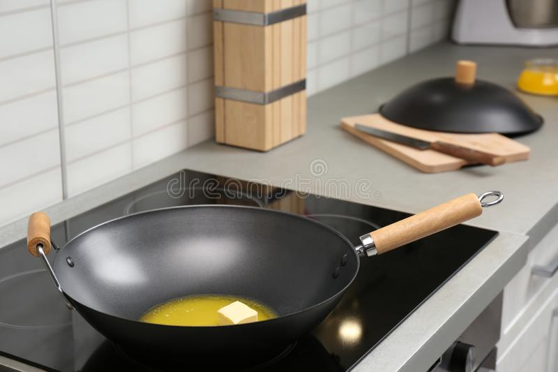 Wok pan with melted butter on stove royalty free stock photo