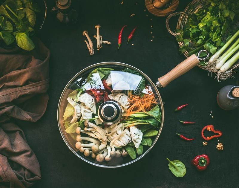 Wok pan with vegetarian korean hot pot with vegetables and dumplings  on dark rustic kitchen table background with ingredients, royalty free stock photography