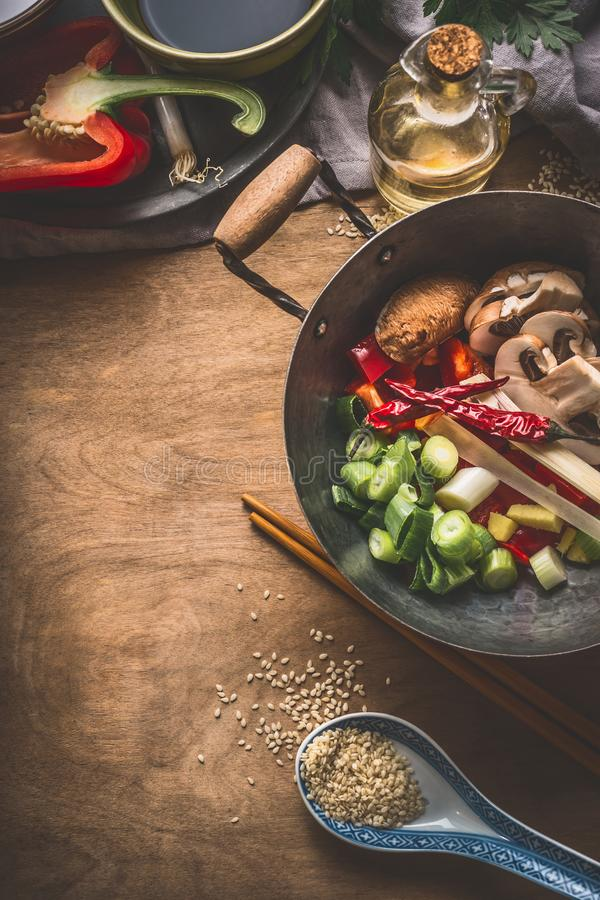 Wok pot with vegetarian asian cuisine ingredients for stir fry with chopped vegetables, spices, sesame seeds and chopsticks on rus stock images