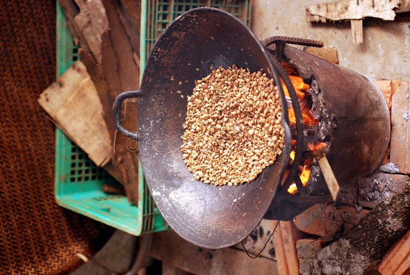 Wok Roasting Coffee. Wok roasting organically grown, green coffee beans from the Bolaven Plateau over a wood fire in Laos stock image