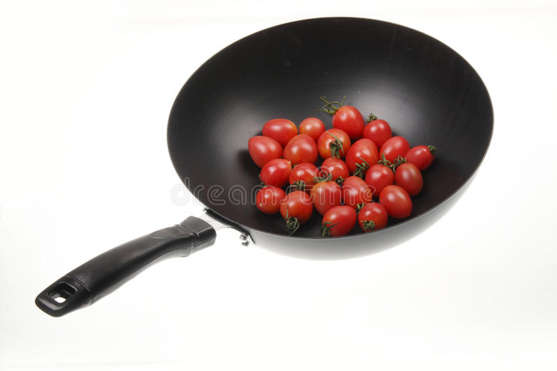 Wok with tomato. Chinese wok with small tomatoes on white stock image