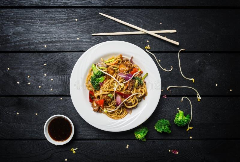 wok Udon beweegt gebraden gerechtnoedels met kip en groenten in een witte plaat op zwarte houten achtergrond Met eetstokjes en royalty-vrije stock foto