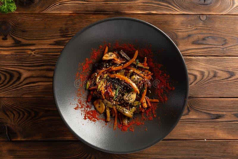 Wok warzywa z pikantność w czarnym talerzu fotografia stock