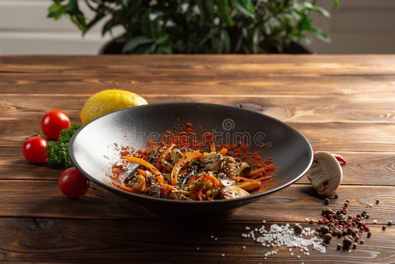Wok warzywa z pikantno?? w czarnym talerzu fotografia royalty free