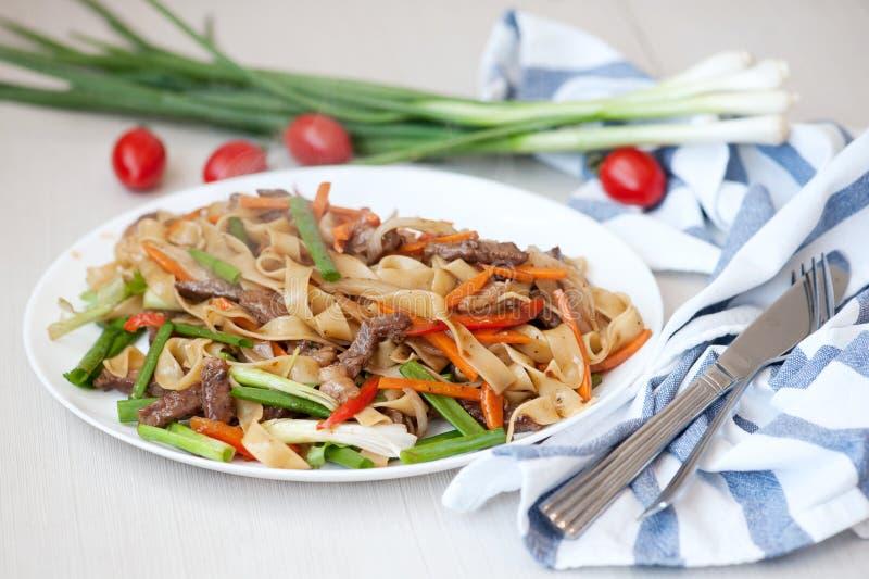 woka Nudlar med kött och grönsaker i kines arkivbilder