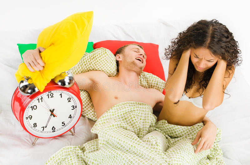 Woke up difficulties at monday. Young couple annoyed by big alarm clock at monday morning royalty free stock image