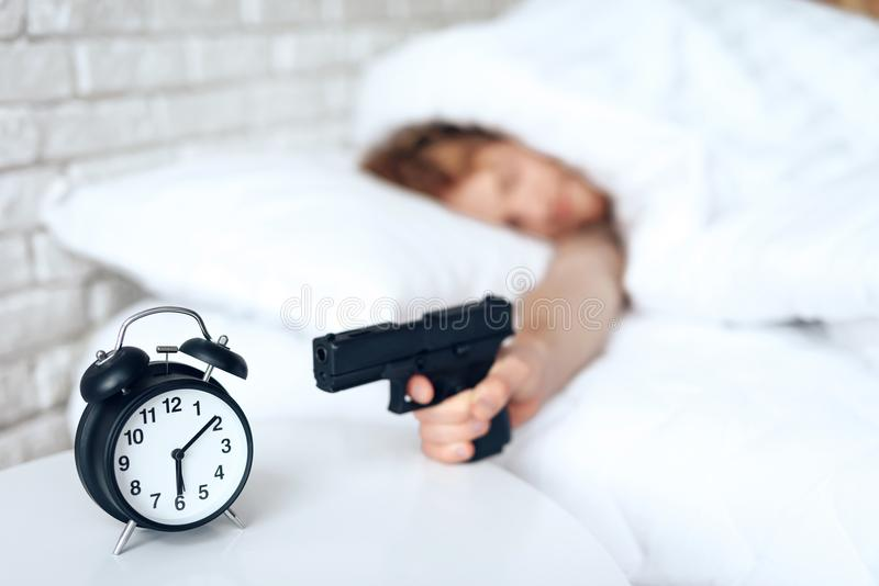 Woken up man is aims gun at alarm clock royalty free stock images