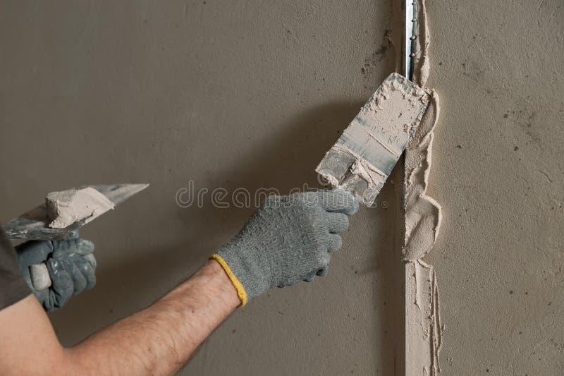 Woker fixe un guide pour aligner les murs avec le stuc photos stock