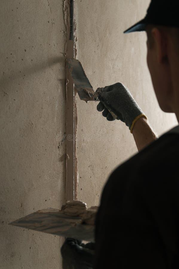 Woker fixe un guide pour aligner les murs avec le stuc photo libre de droits