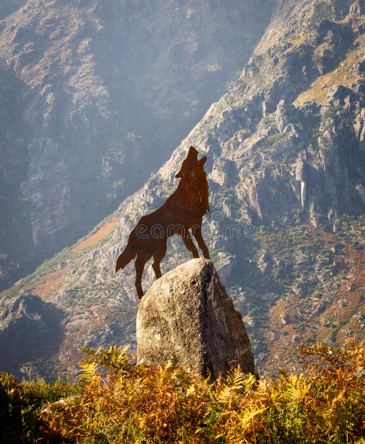 Wolf Howling Brass Figure sobre a rocha fotos de stock royalty free