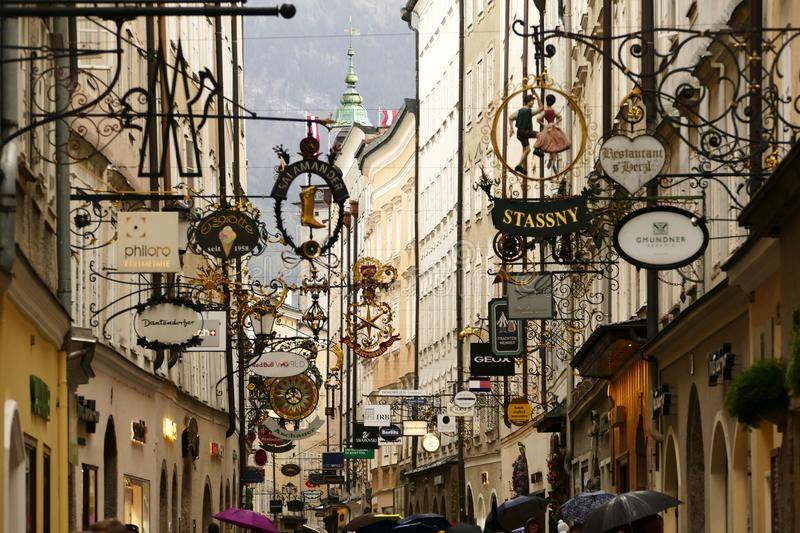Salzburg, Austria - Oct 9, 2017: Famous downtown street Getreidegassewith many wrought iron signs in the autumn rain. Wolfgang Amadeus Mozart was born in this royalty free stock photos