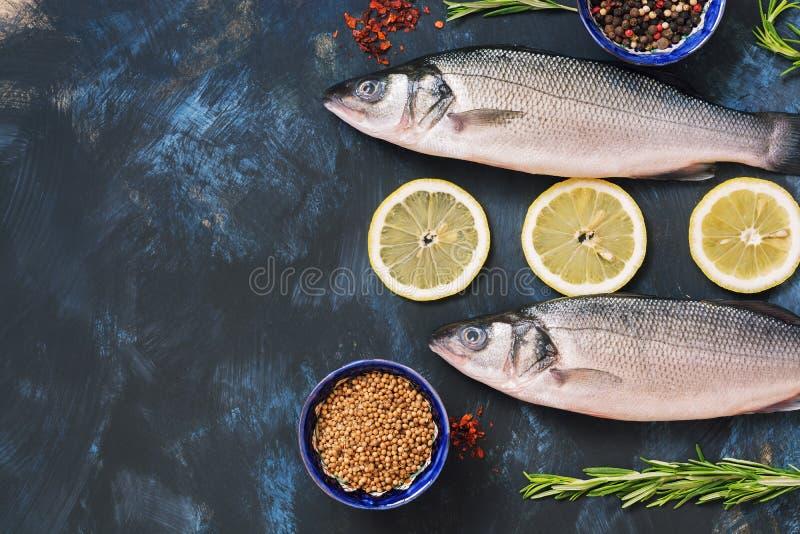 Wolfsbarsch und Bestandteile der frischen Fische für das Kochen - Zitrone, Rosmarin, grüner Pfeffer, sumac, Koriander, Paprika Ro stockbilder