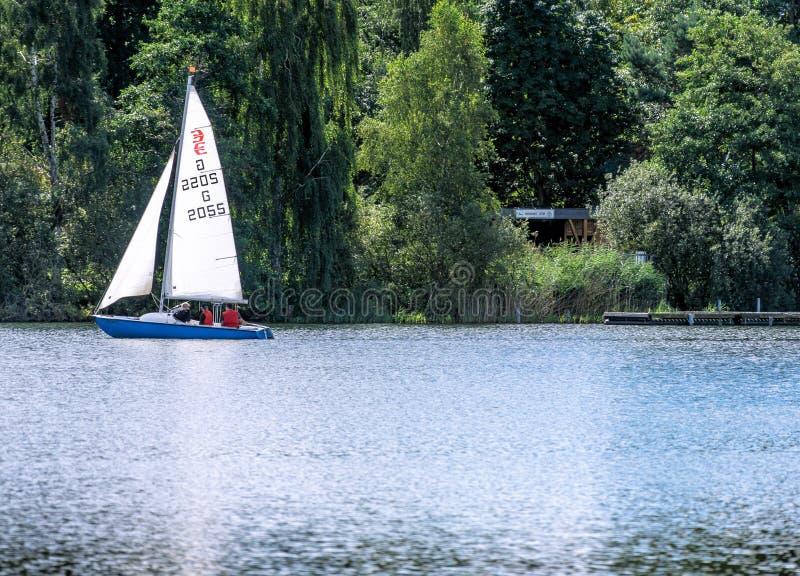 Wolfsburgo, Baja Sajonia, Alemania - 13 de agosto de 2017: Un pequeño barco de navegación con tres pasajeros flota en un lago fotografía de archivo libre de regalías