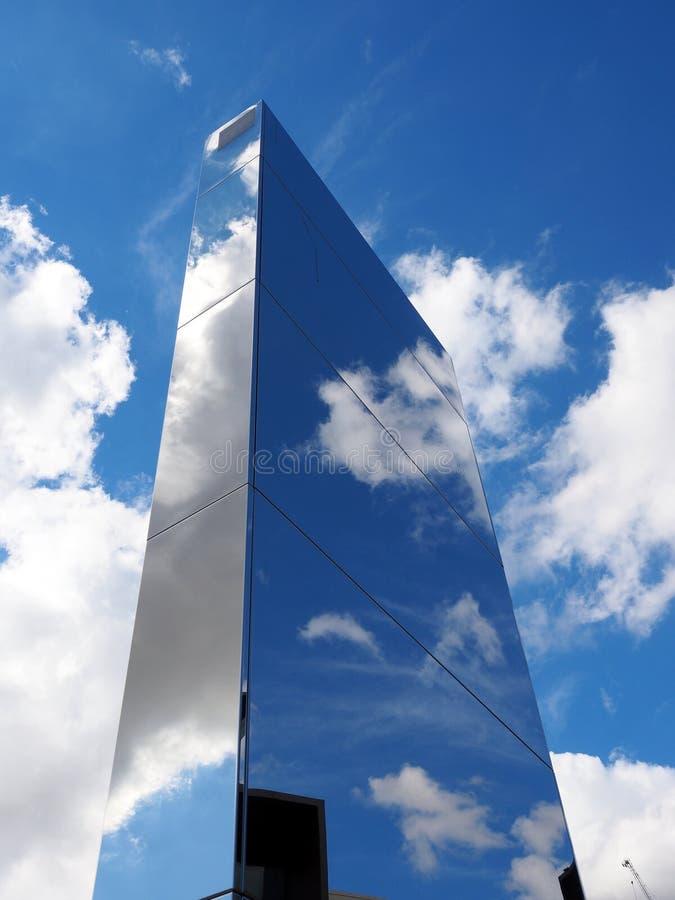 Wolk en Blauwe Hemelbezinningen over de voorgevel van het Wolkenkrabberglas royalty-vrije stock foto