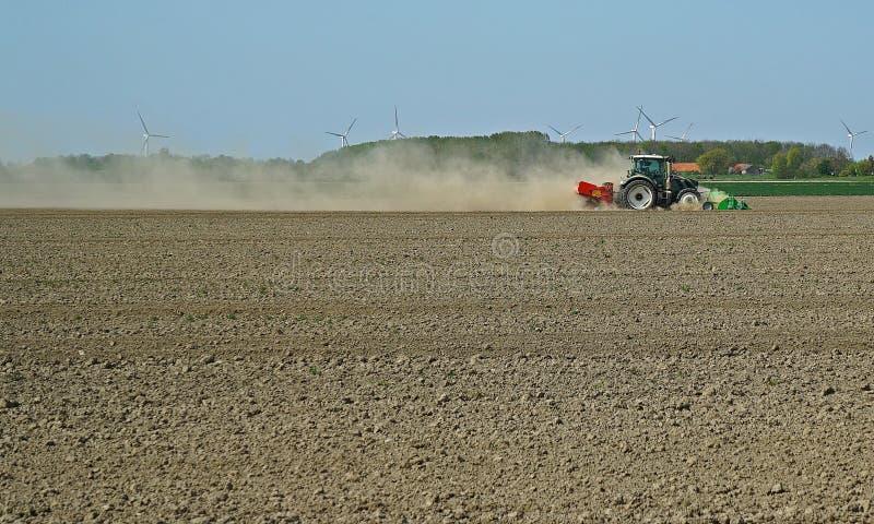 Wolk van stof achter een ploegende tractor tijdens de lente in Zeeland stock afbeeldingen