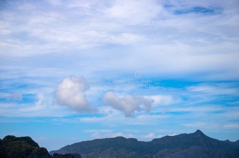 Wolken auf blauem Himmel und Bergen Tropeninselschattenbild Tropisches cloudscape Foto Flaumige Wolke auf blauem Himmel stockfotos