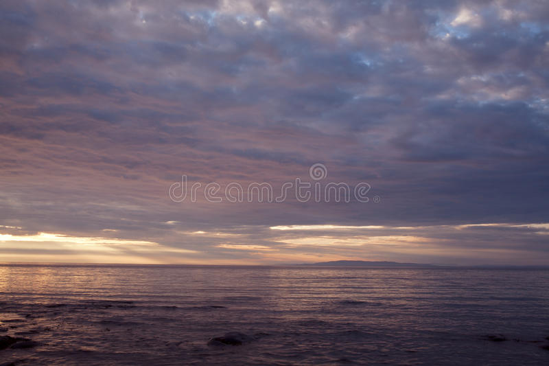 Wolken bei Sonnenuntergang über dem Meer stockbild