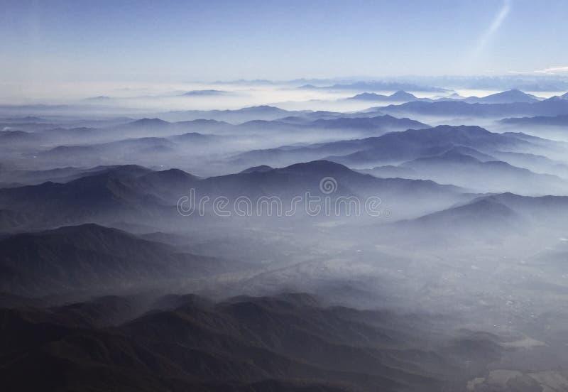 Wolken bleiben über den Hügeln zurück, die in Abstand ausdehnen, wie fotografiert vom Flugzeugfensterfliegen über Chile lizenzfreies stockfoto