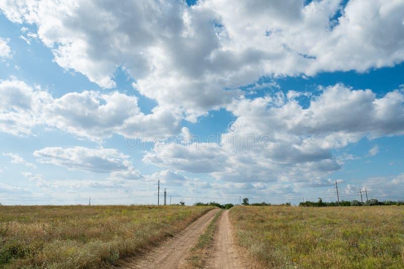 Wolken des Sandschotterwegwegweisenfeldwiesenlandschaftsblauen Himmels stockfoto
