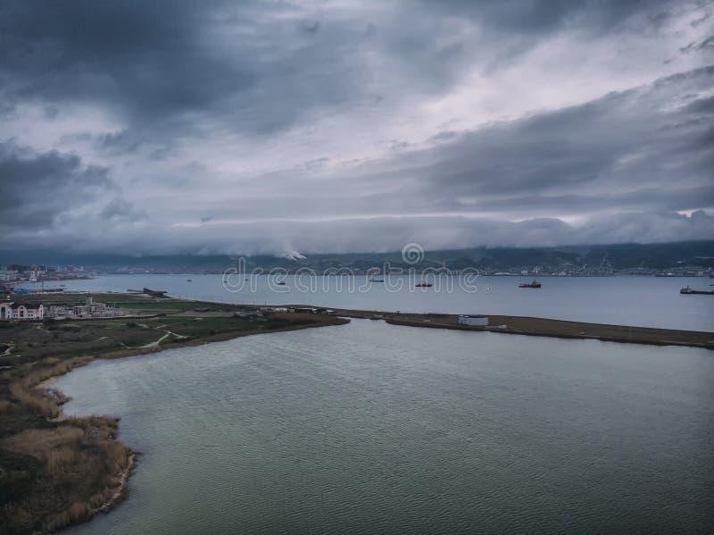 Wolken, die ?ber den Bergen, regnerisches Wetter in der Stadt von Novorossiysk h?ngen Ansicht der Cemes-Bucht, der Hafen und stockfotos