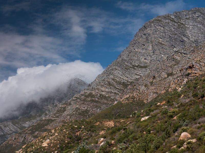 Wolken die over bergbovenkanten krullen langs de Westelijke Kaapkust in Zuid-Afrika stock fotografie