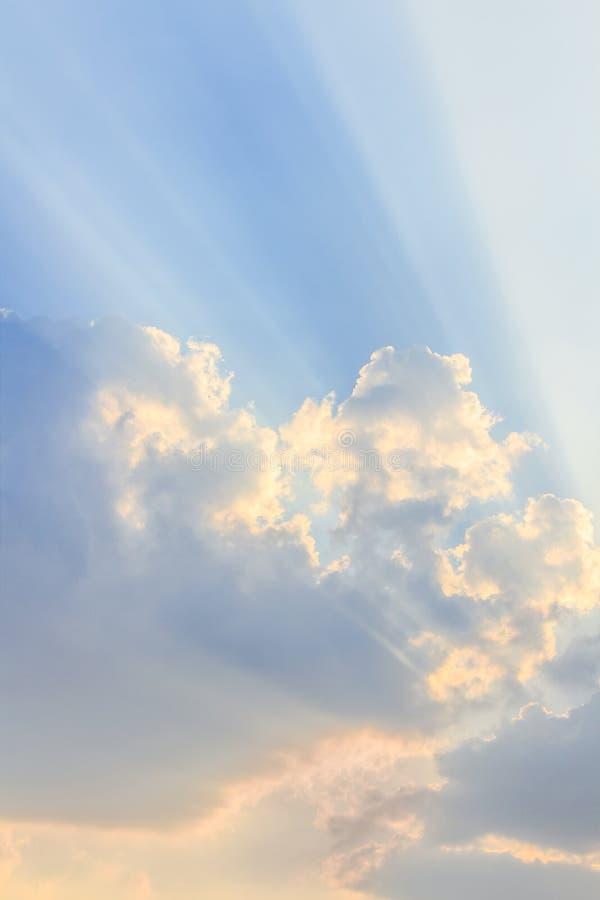 Wolken en een blauwe hemel met een zonnestraal die door glanst stock afbeeldingen