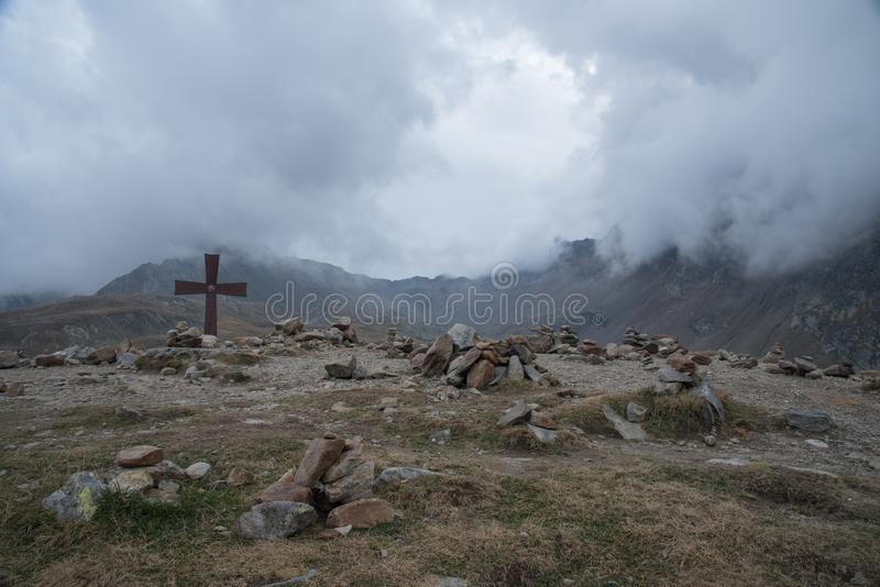 Wolken en kruis bij bergen stock foto