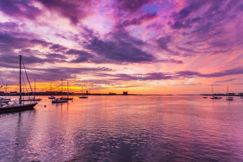 Wolken en levendige zonsopgangkleuren over de Haven van Boston stock fotografie