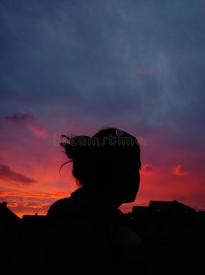 Wolken en purpere zonsondergang en een meisje stock foto