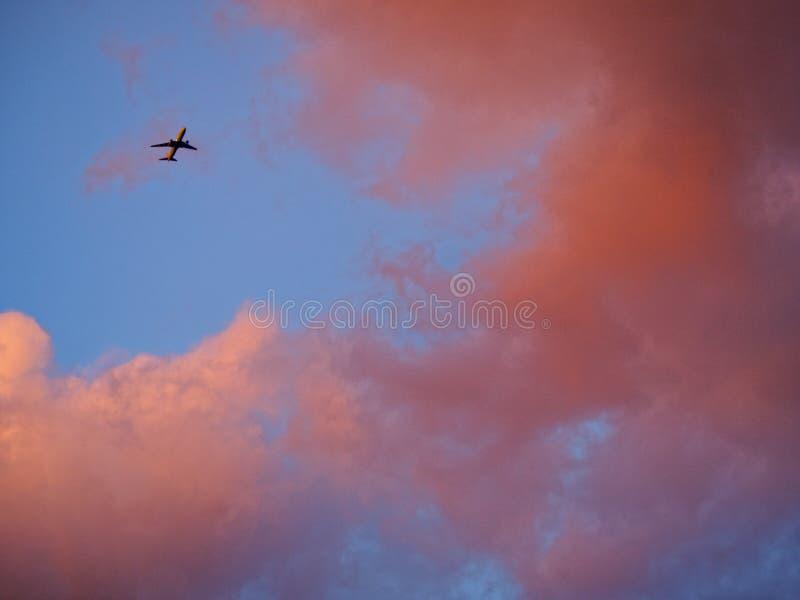 Wolken en vliegtuigen in de hemel bij zonsondergang royalty-vrije stock foto's