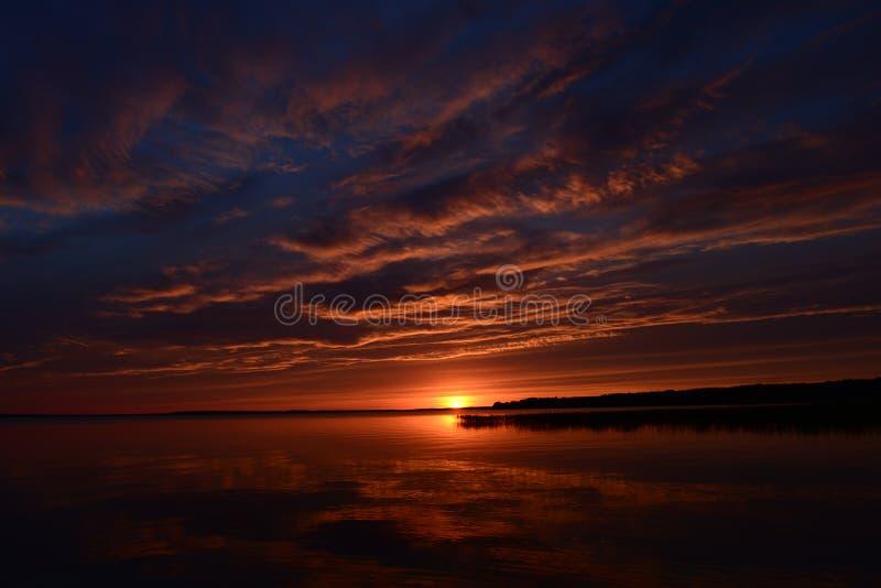 Wolken en zonsondergang het water bij schemer worden overdacht die stock afbeelding