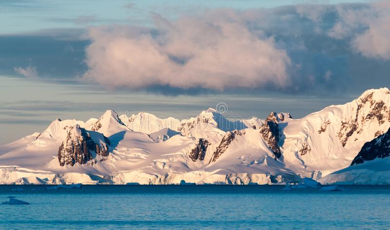 Wolken en zonsonderganglicht over snow-capped bergen en ijsbergen, Antarctisch Schiereiland stock foto