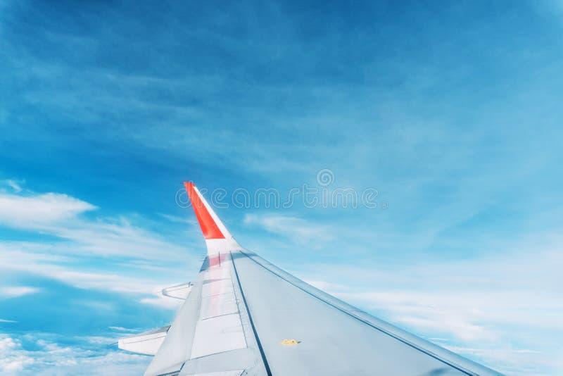 Wolken-, Himmel- und Flügelflugzeug als gesehenes durch Fenster eines Flugzeuges stockbild