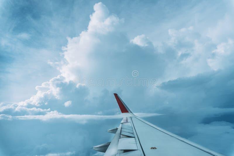 Wolken-, Himmel- und Flügelflugzeug als gesehenes durch Fenster eines Flugzeuges stockfotos