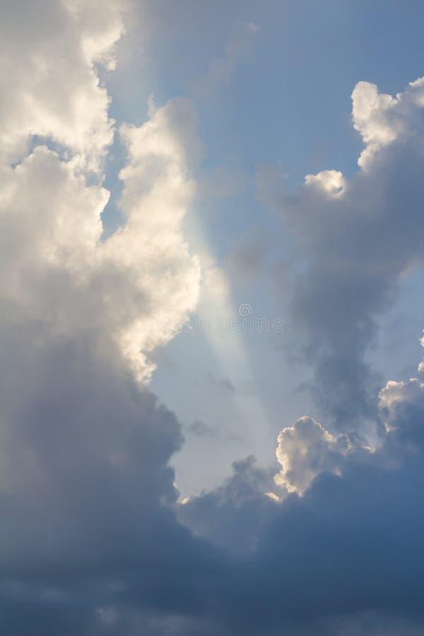 Wolken op blauwe die hemel door verticale straal van zonlicht wordt doordrongen, royalty-vrije stock afbeelding