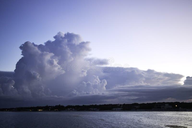 Wolken over kuststad bij schemer royalty-vrije stock afbeeldingen