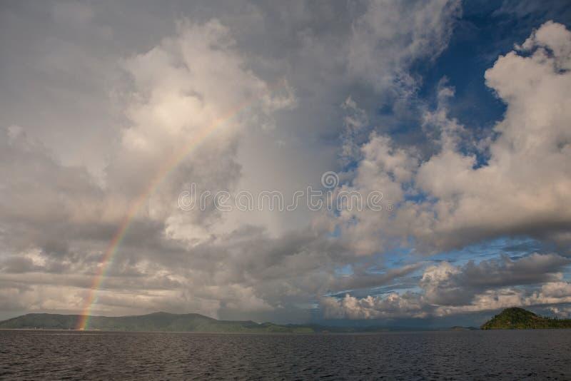 Wolken, Regenbogen und Inseln stockbild