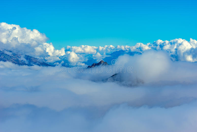 Wolken umfassen die Gebirgsoberteile lizenzfreies stockbild