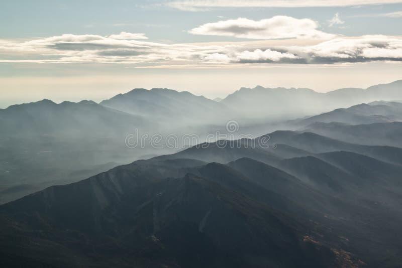 Wolken und Dunst über Gebirgszug stockfotos