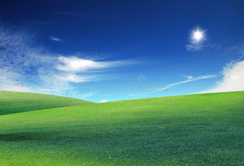 Wolken und ein grünes Feld lizenzfreie stockbilder
